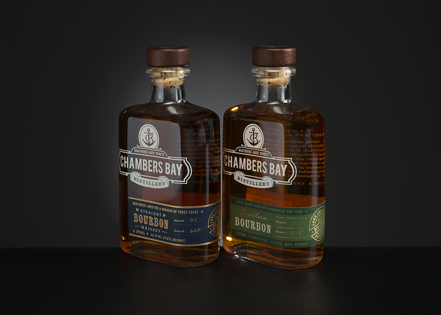 Product photo of bottles with brown bourbon on a black background.