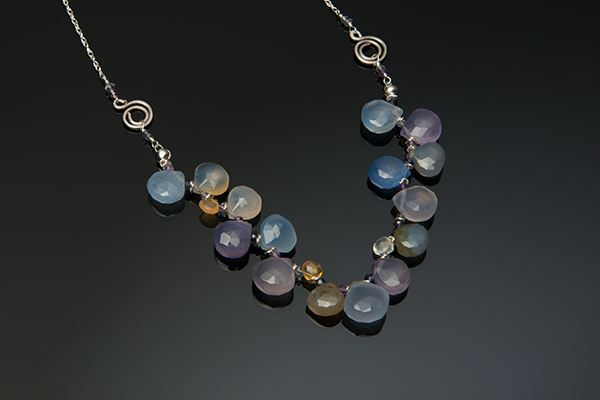 multicolored gemstone necklace jewelry photography on a black reflective surface