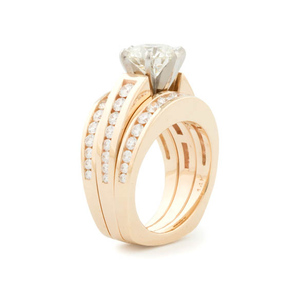 product photograph of gold ring with large diamond set with three rows of smaller diamonds along the sides on weight background