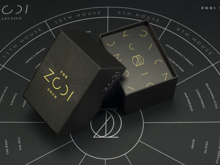 product photography of black board game with close up on open card box with gold text