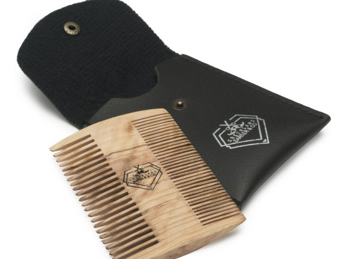 Product product photography wooden comb resting on lather pouch with pure white background.