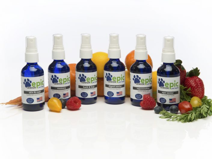Product photography of small blue glass spray bottles fanned out with various fruits and vegetables on a reflective white background