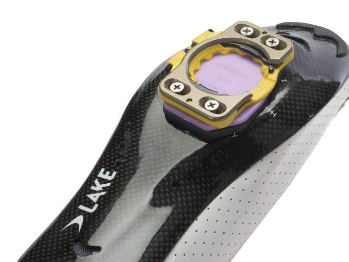 Product photograph of the shiny black bottom of bycicle shoe with yellow and purple toe clip